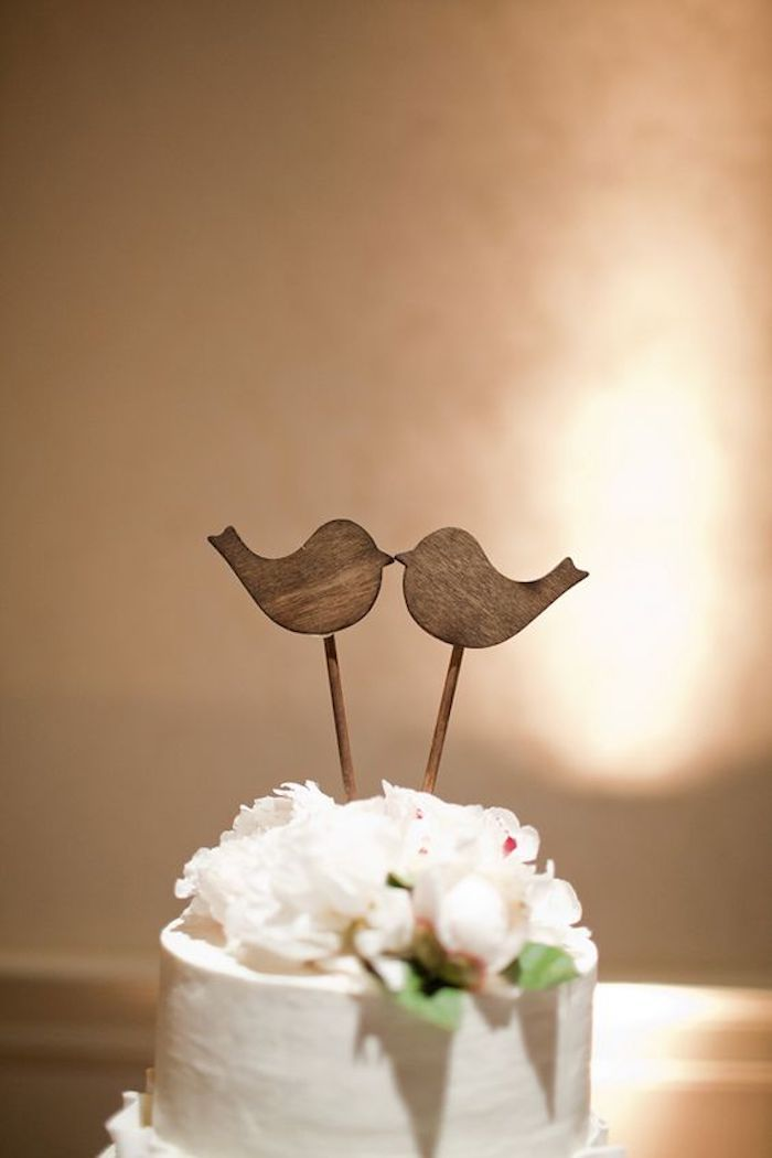The wooden birds combine rusticity and romanticism in the wedding cake
