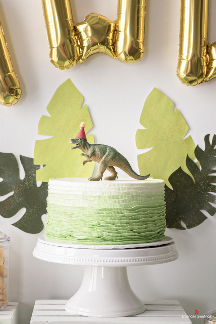 A toy dinosaur graces the top of the birthday cake