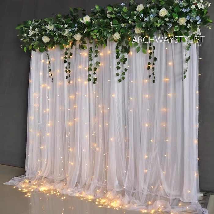 Fluid white fabric, string of small lights and fresh vegetation: an idea that goes well with wedding parties.