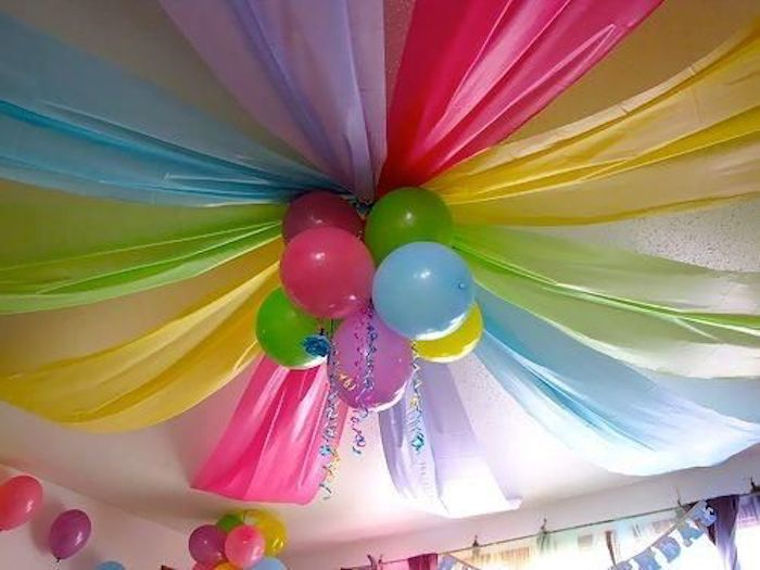 Colorful fabrics and balloons decorate the birthday party.