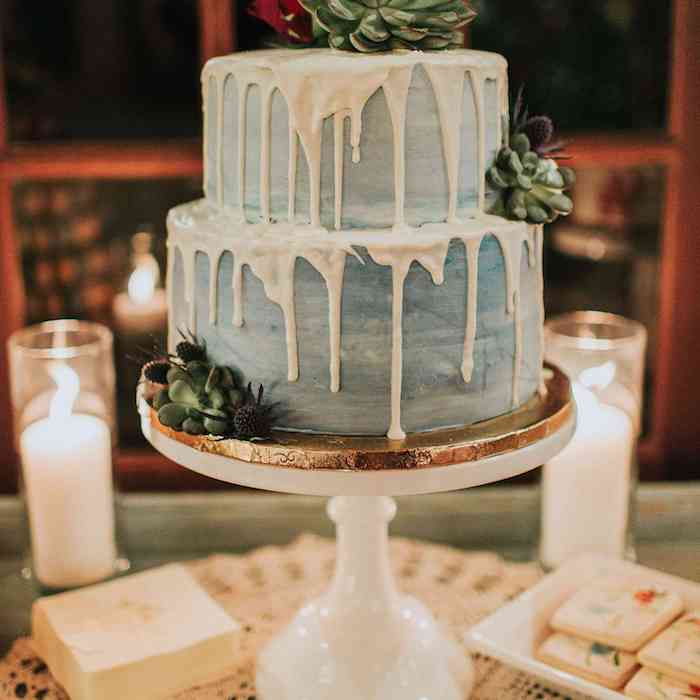 Double-decker cake with dripping effect and decorated with succulents