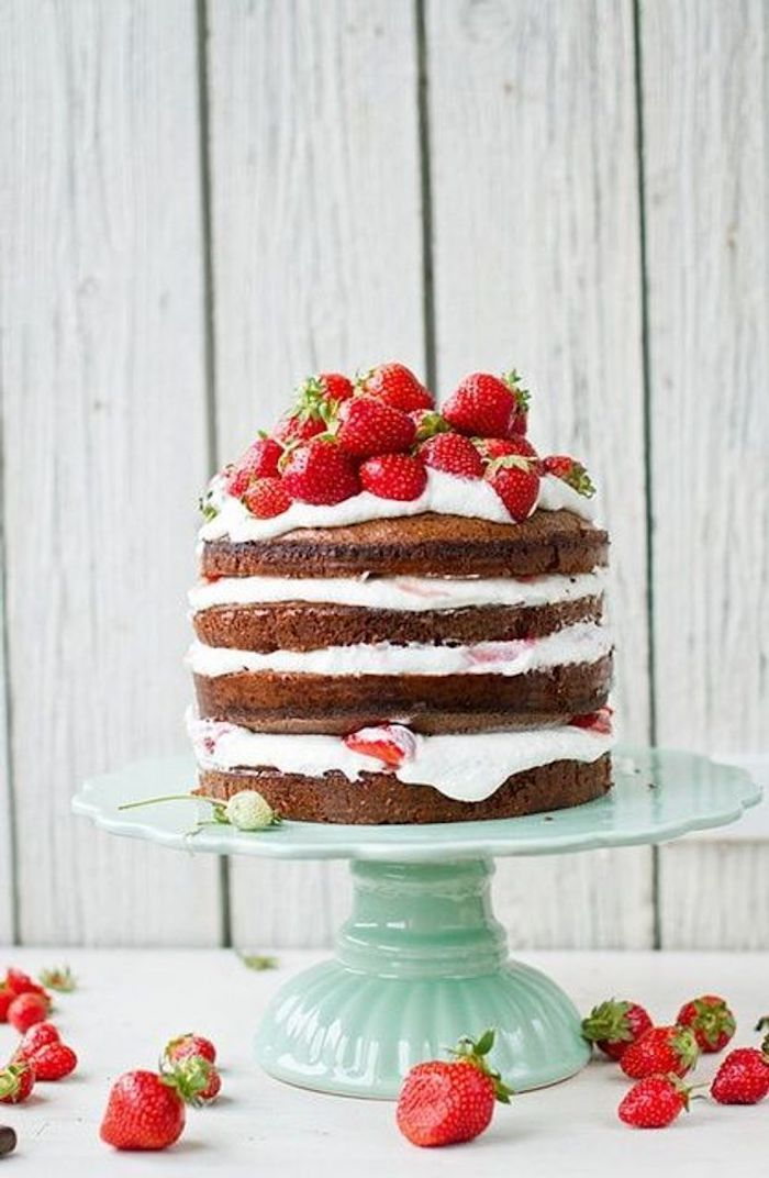 Naked cake decorated with whipped cream and strawberries