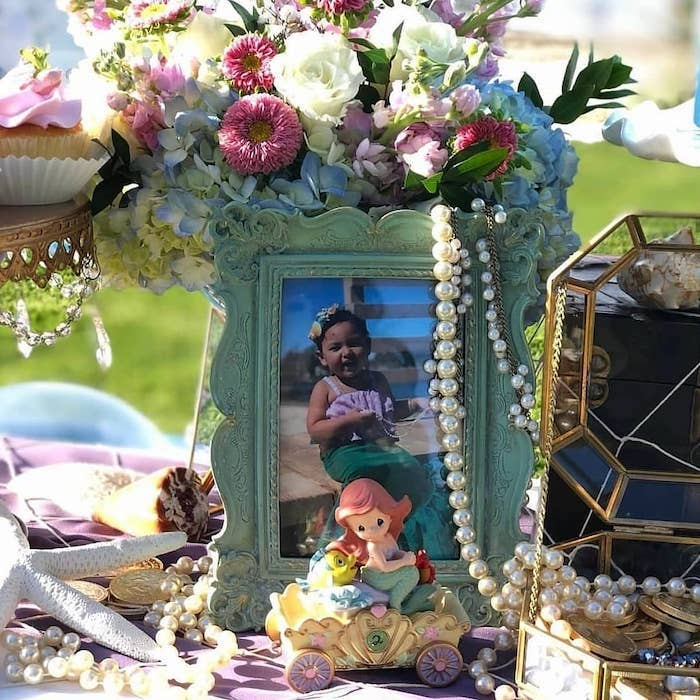 The photo of the birthday girl placed in a beautiful frame decorates the birthday table