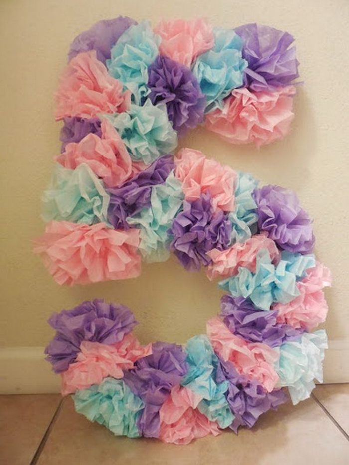 Crepe paper in lilac, light blue and pink colors adorn the age of the birthday girl