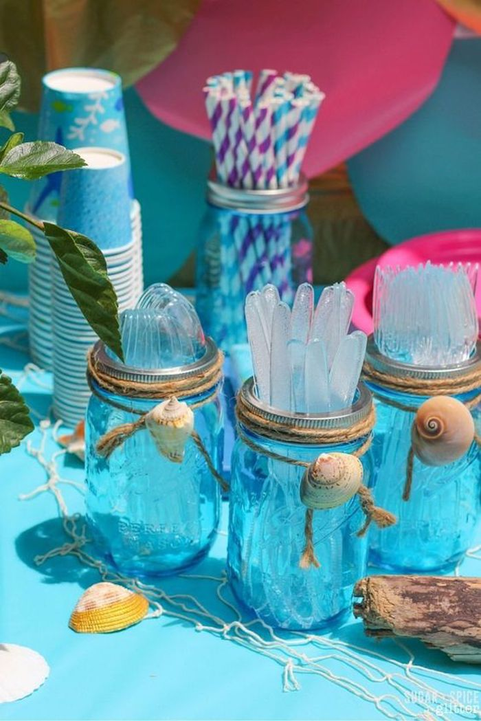Glass jars decorated with shells to place the cutlery