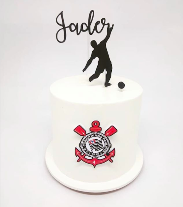 A small, all-white cake, with the silhouette of a player on top